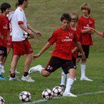 Ragazzi si allenano nel tiro in porta durante il Milan Camp