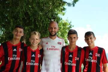 Quattro ragazzi con il loro allenatore alla scuola calcio estiva del Milan