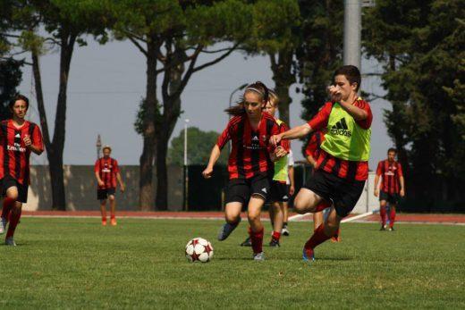 Ragazze e ragazzi giocano a calcio al campo estivo dell'AC Milan