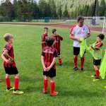 Stefano Eranio with eight children on playing field of the AC Milan Academy Camp