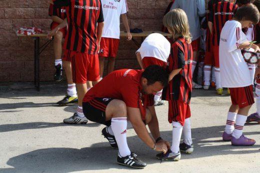 Lo staff AC Milan Sporteventi aiuta un bambino ad allacciarsi le scarpe da calcio e con il materiale sportivo