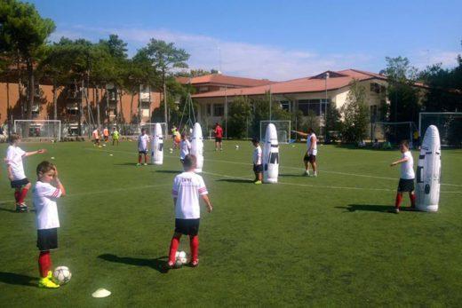 Meninos e meninas jogam futebol com engrenagens técnicas de alta qualidade no AC Milan Junior Camp Sporteventi