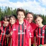 Former footballer Stefano Eranio embraces four kids he trains during AC Milan summer football school