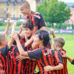 Teens celebrate their teammate's goal during the AC Milan Academy Junior Camp