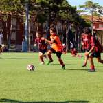 Five children engaged in a football action during training in the AC Milan Academy Camp