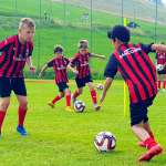Five children with AC Milan shirts engaged in training during training on the summer football camp
