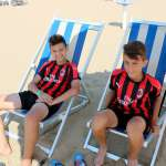 Two boys of the AC Milan summer camps sitting on the beach chairs in Lignano Sabbiadoro