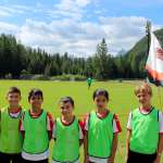 Seven children of the AC Milan Academy Camp in front of the playing field of Cortina d'Ampezzo in the Dolomites