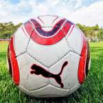 Soccer ball on the synthetic turf of the playing field of the AC Milan Academy Camp in Lignano Sabbiadoro