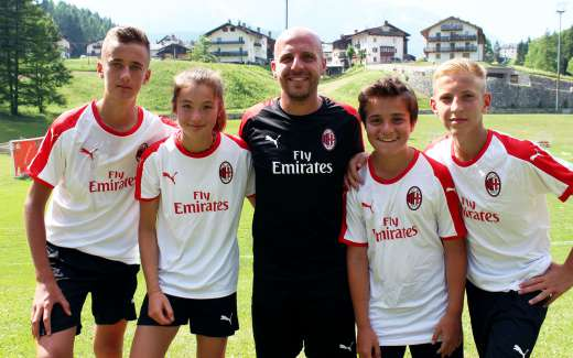 A member of the Sporteventi staff with three boys and a girl during the day at the AC Milan Academy Camp